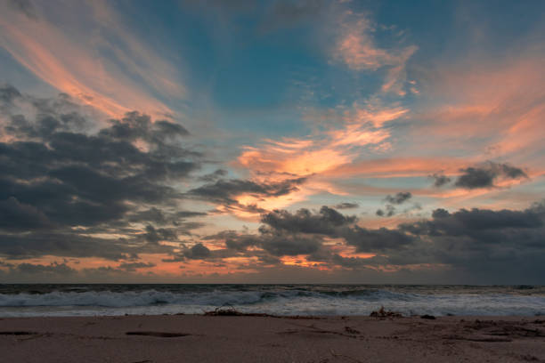 colorful clouds over the ocean at sunrise stock photo