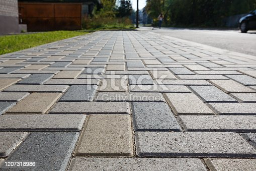 Colorful cobblestone road pavement and lawn divided by a concrete curb. Backlight. Diminishing perspective.