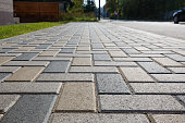 istock Colorful cobblestone road pavement and lawn divided by a concrete curb. Backlight. 1207318986