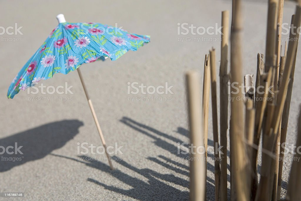 colorful cocktail umbrella in the sand royalty-free stock photo