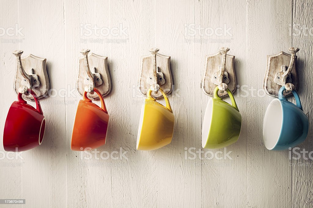 Colorful coffee cups on hooks royalty-free stock photo