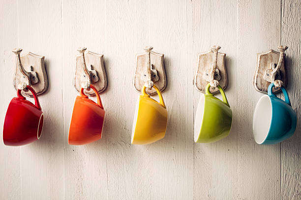 Colorful coffee cups on hooks stock photo