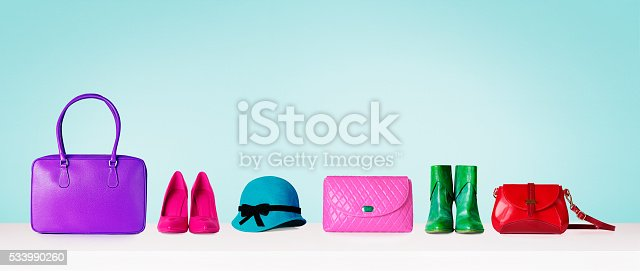 istock Colorful collections of bags and purses. Isolated on blue. 533990260