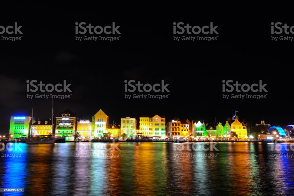Evening lights reflect candy-colored buildings on the waterfront at...