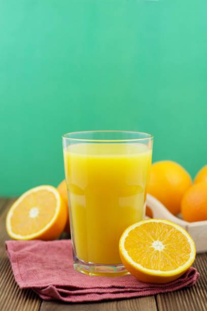 bunte komposition mit einmachglas glas voll frisch gepressten orangensaft mit stroh, obst, isoliert auf grünem hintergrund. nahaufnahme, raum, ansicht von oben kopieren. - pop up stock-fotos und bilder