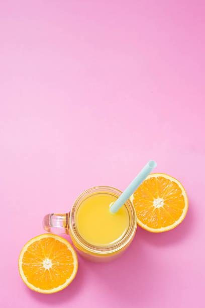 bunte komposition mit einmachglas glas voll frisch gepressten orangensaft mit stroh, obst, isoliert auf rosa hintergrund. nahaufnahme, raum, ansicht von oben kopieren. - pop up stock-fotos und bilder
