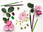 Colorful composition with roses and painting accessories. Flat lay