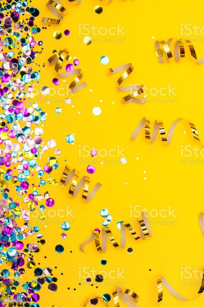 Confetes coloridos e serpentinas espiral douradas sobre fundo amarelo - foto de acervo
