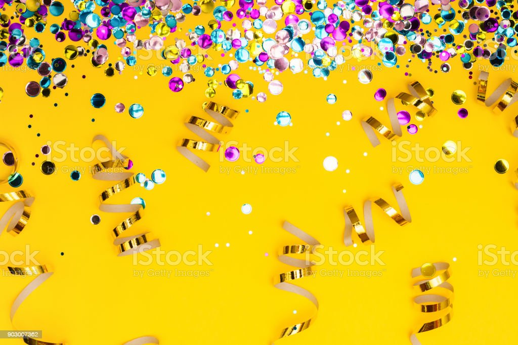 Colorful confetti and golden coiled streamers on yellow background stock photo