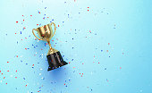 istock Colorful Confetti Falling over Gold Cup Sitting over Blue Background 1238090761
