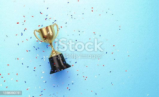 Colorful confetti falling over gold cup sitting over blue background. Horizontal composition with copy space. Directly above.