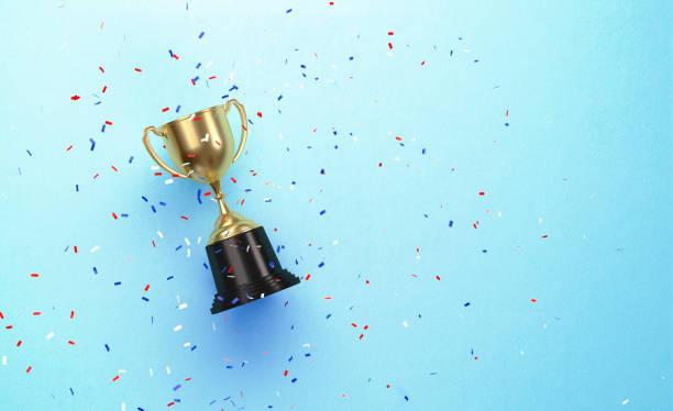 五顏六色的紙屑落在金杯坐在藍色背景 - 成功 個照片及圖片檔