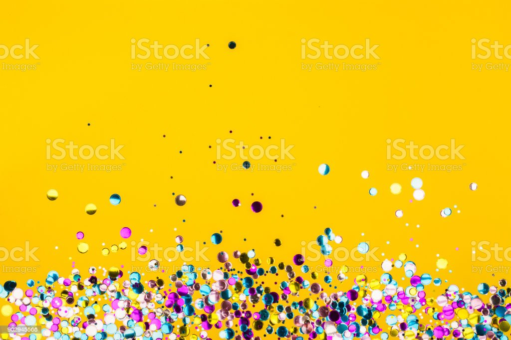 Colorful confetti on yellow background - foto stock
