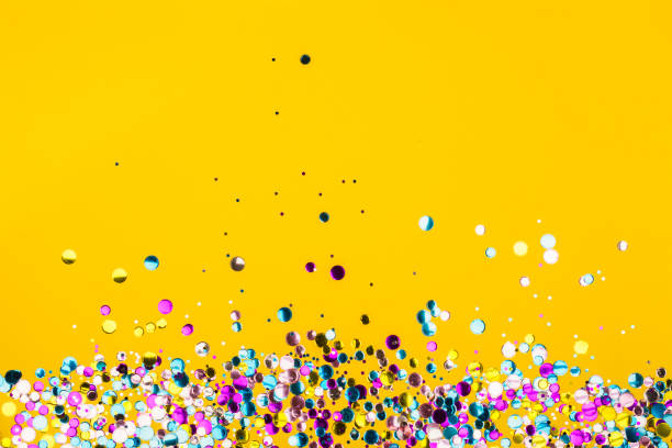 Colorful confetti on yellow background stock photo