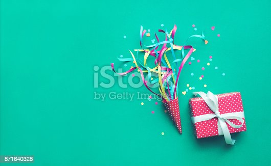 istock Colorful confetti,streamers and gift box on green color 871640328