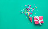 Colorful confetti,streamers and gift box on green color
