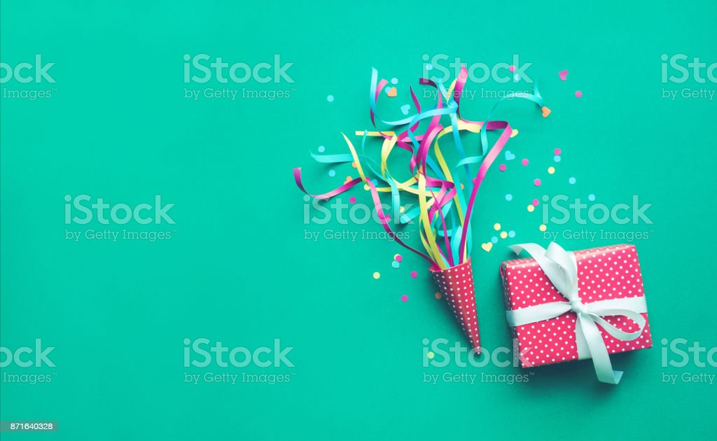 Colorful confetti,streamers and gift box on green color stock photo