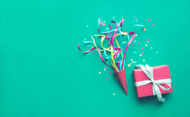 colorful confetti,streamers and gift box on green color - birthday gift stock photos and pictures