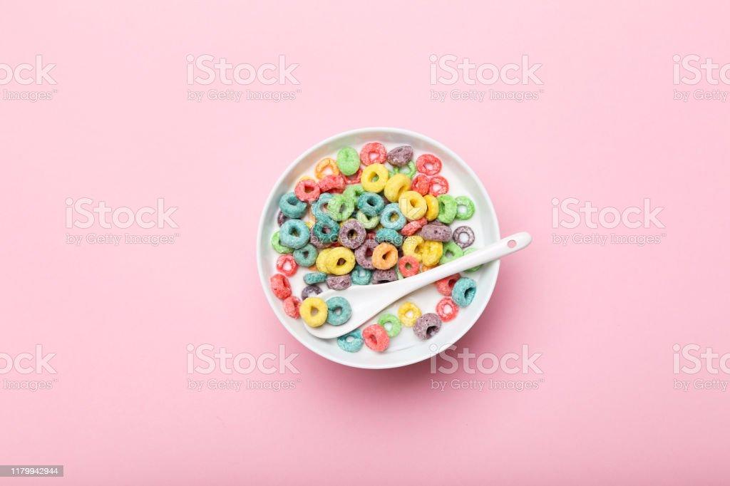 Bunte Maisringe in Schüssel mit Milch und Löffel auf rosa Hintergrund - Lizenzfrei Ausgedörrt Stock-Foto