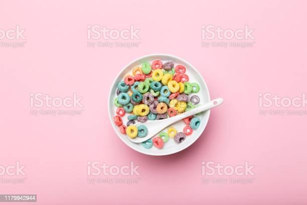 Bunte Maisringe In Schüssel Mit Milch Und Löffel Auf Rosa Hintergrund Stockfoto und mehr Bilder von Ausgedörrt