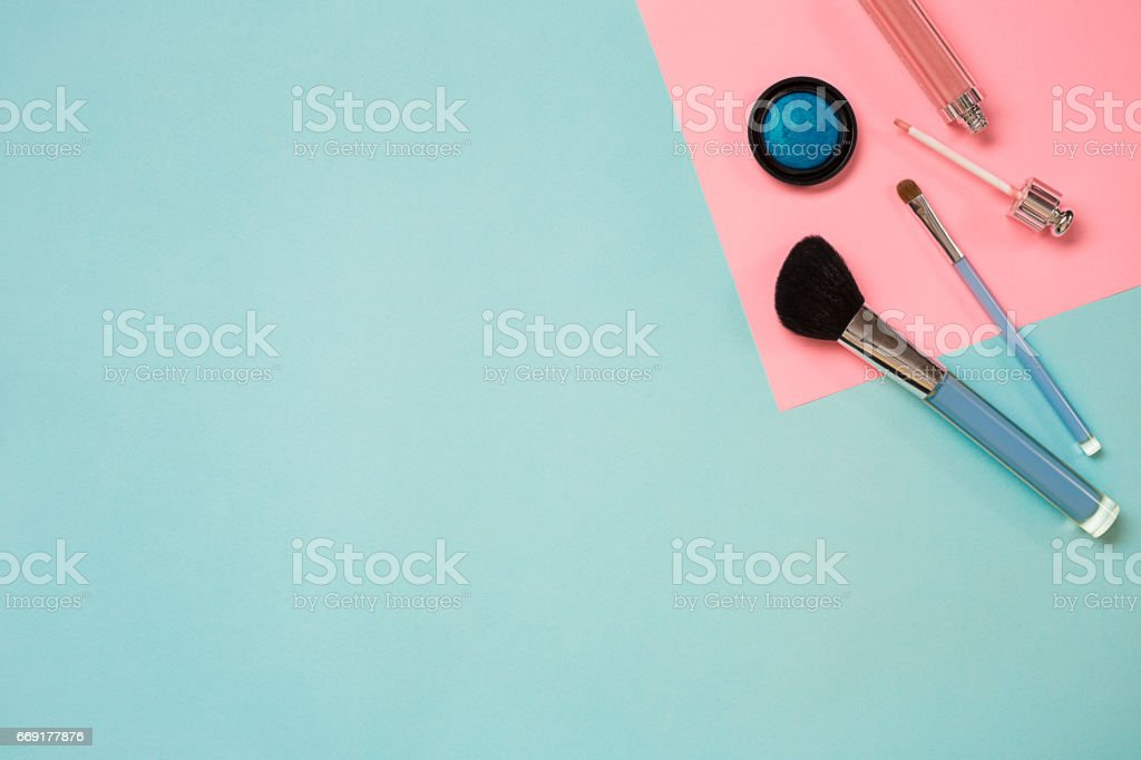 Colorful cosmetics on blue workplace with copy space. Cosmetics make up artist objects: lipstick, eye shadows, powder, tools for make-up.Top view stock photo