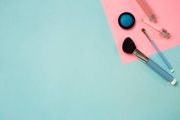bunte kosmetika auf blauen arbeitsplatz mit textfreiraum. kosmetik make-up künstler objekte: werkzeuge für make-up, puder, lidschatten, lippenstift. ansicht von oben - rotes oberteil stock-fotos und bilder