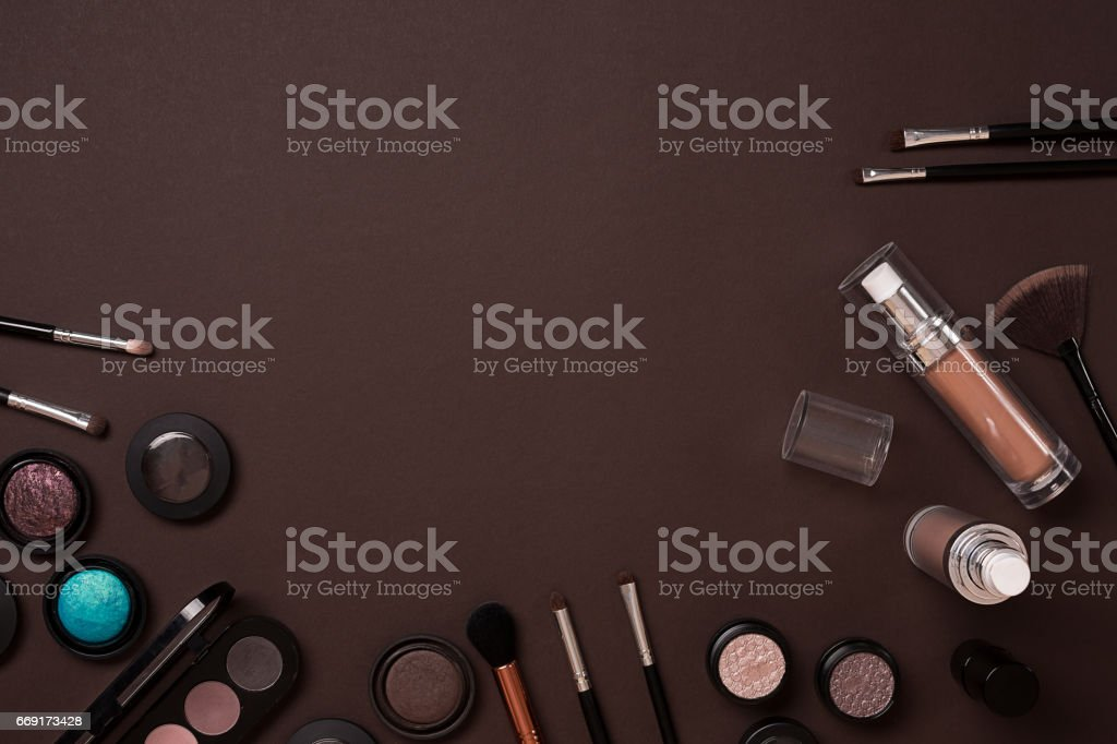 Colorful cosmetics on brown workplace with copy space. Cosmetics make up artist objects: lipstick, eye shadows, powder, tools for make-up.Top view stock photo