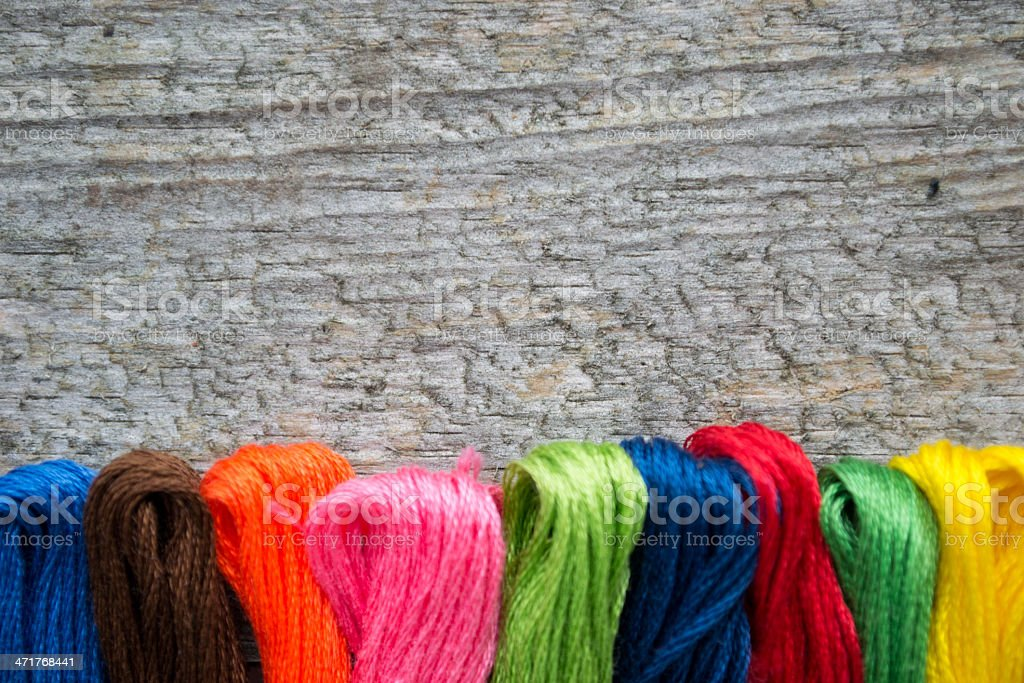 Colorful cotton craft threads on wood background with copy space royalty-free stock photo