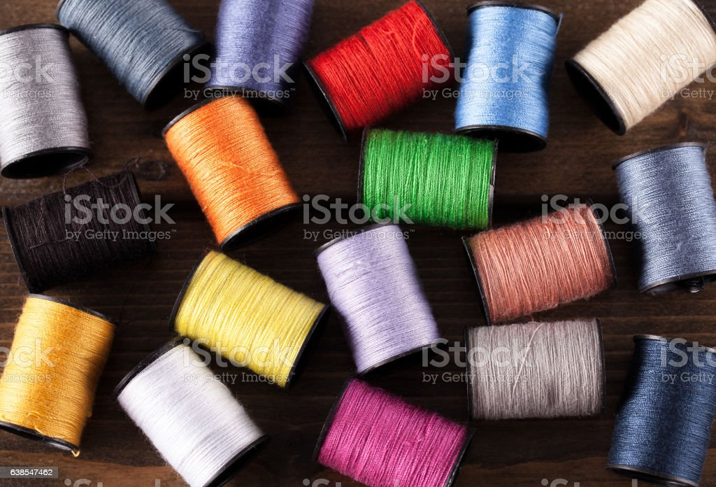 Colorful cotton reels scattered on dark wood stock photo