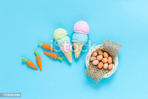 Colorful craft item on blue paper texture background, mini carrot with ice cream and eggs in the basket, food craft object