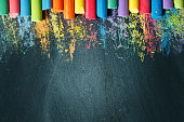 Colorful crayons on the blackboard, drawing. Back to school background