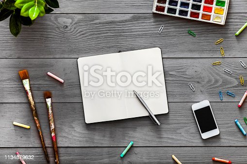 1134879628 istock photo Colorful creative artist table with blank notebook for work sketches and paints, art paintbrushes supplies set on grey wooden background, top view, copy space, flat lay style, drawing class education 1134879632