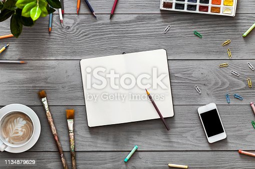 1134879628 istock photo Colorful creative artist table with blank notebook pencil paints for work sketches, art paintbrushes supplies set on grey wooden background, top view, copy space, flat lay, drawing class education 1134879629