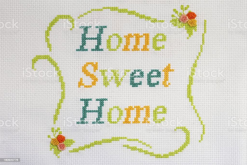 Colorful cross-stitch saying home sweet home with flowers stock photo