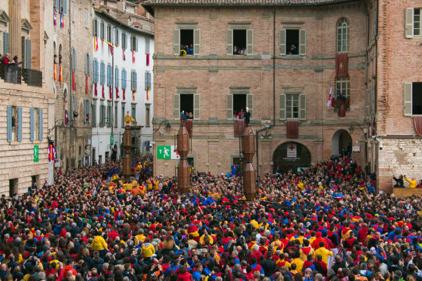 Colorful crowd participating in the 'Feast of Ceri or candles race', a traditional event of the city of Gubbio, a well preserved medieval town the 15th of may 2017 in Gubbio Gubbio, Italy - May 15, 2017: The Corsa dei Ceri or the candle race takes place every year on May 15th on the eve of the feast of the city's patron saint, St. Ubaldo in the medieval town of Gubbio in Umbria . The statues of St. Ubaldo (patron of bricklayers), St. George (patron saint of haberdashers) and St. Anthony the Abbot (patron saint of donkey breeders and peasants) are placed on 3 tall, heavy wooden ceri or pedestals (meant to represent candles). The event consists of a race. Ceraioli (pedestal bearers) carry the ceri on their shoulders and run down the city streets and then up to the basilica of S. Ubaldo on top of Mount Ingino. A charming ritual precedes the race. In this photo you can see the rase of the three big ceri or candles in Piazza della Signoria of Gubbio in Umbria, Italy. piazza grande stock pictures, royalty-free photos & images