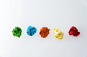 Colorful crumpled paper balls on white background