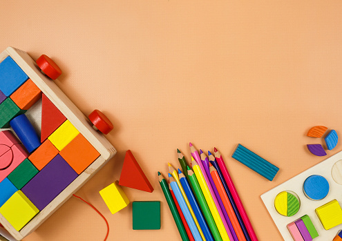 Colorful cubes, paints, pencils, blocks, modeling clay on orange background. Interesting math, games for preschool for kids. Education, back to school concept