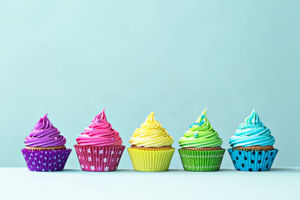 Colorful cupcakes Row of colorful cupcakes on blue cupcake stock pictures, royalty-free photos & images
