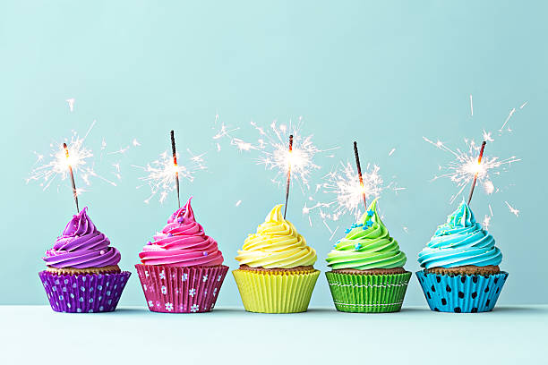 Colorful cupcakes with sparklers Row of colorful cupcakes with sparklers birthday candle stock pictures, royalty-free photos & images