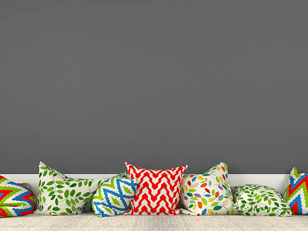 Colorful cushions and a gray wall stock photo