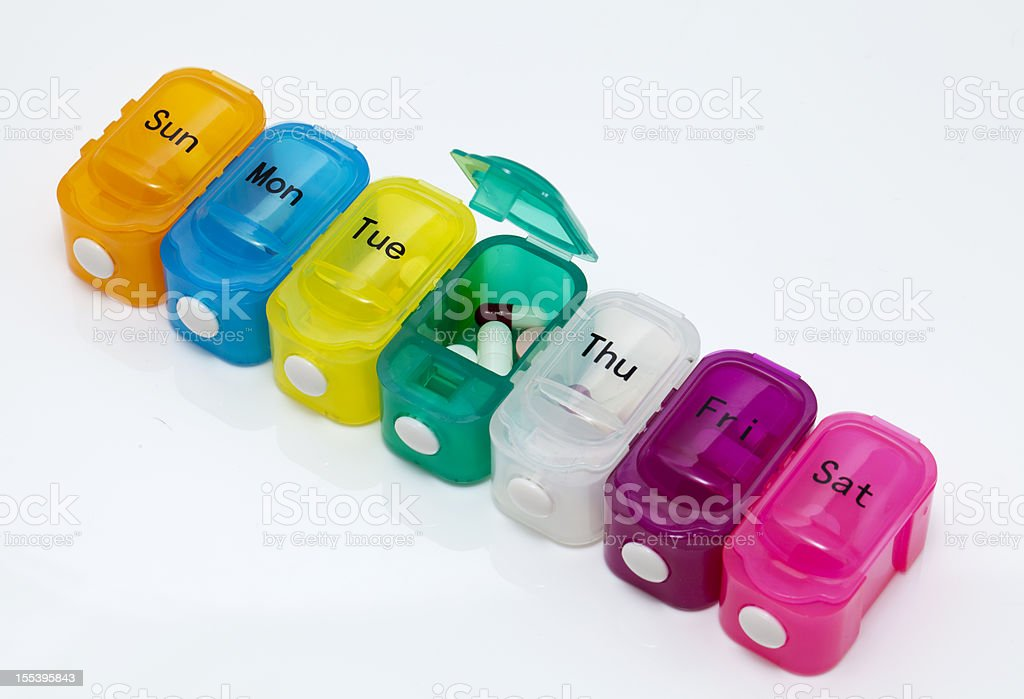 Colorful daily pill organizer on plain white background stock photo