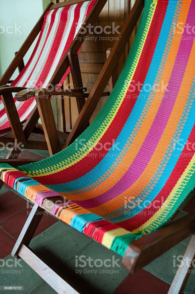 Colorful deck chair in front of a wooden door at stock photo
