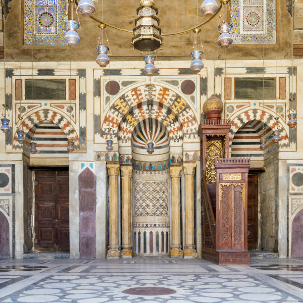Colorful decorated marble wall with Mihrab and wooden minbar at mosque of Sultan Barquq, Cairo, Egypt stock photo