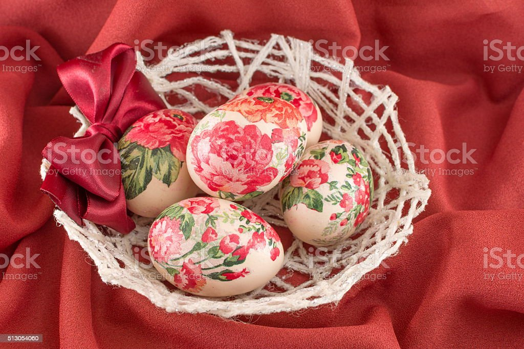 Colorful decoupage decorated Easter eggs on red fabric stock photo