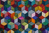 Colorful detail of quilt sewn from diamond pieces