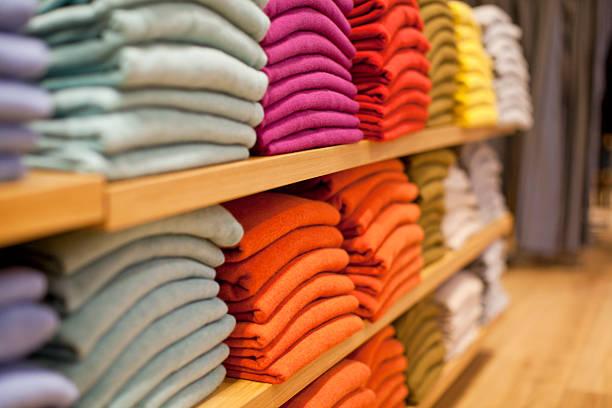 colorful display of sweaters on shelf in store - kledingwinkel stockfoto's en -beelden