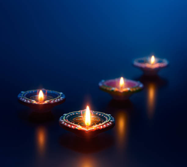 colorful diya lamps lit during diwali celebration - diwali stock pictures, royalty-free photos & images