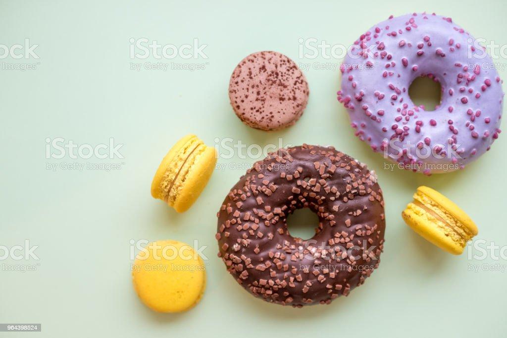 Donuts coloridos e confeitos na mesa de madeira. Vista superior com espaço de cópia. Insalubre, mas saborosa sobremesa - Foto de stock de Azul royalty-free