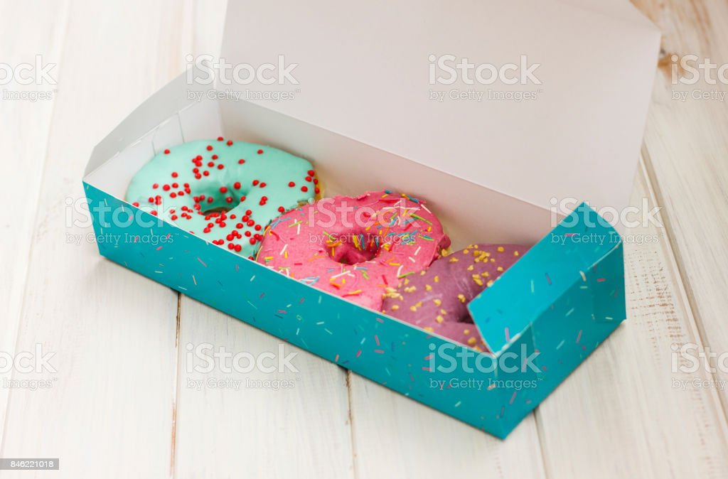 Colorful donuts in the cardboard box on the white wooden background stock photo