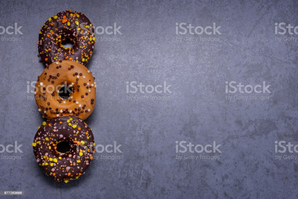 Colorful donuts with chocolate on stone table stock photo